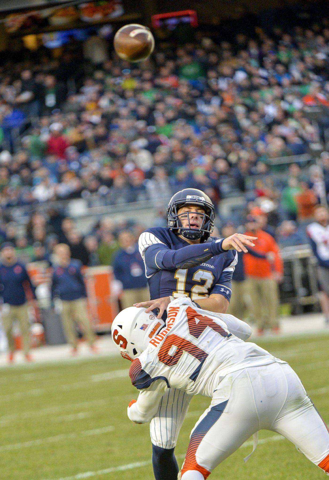 ed60c963d Notre Dame quarterback Ian Book (12) makes throw under pressure from  Syracuse defensive lineman
