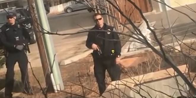 Officer draws gun on black man picking up trash outside his own home